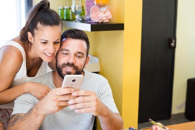 Retrato, de, um, par feliz, usando, telefone móvel