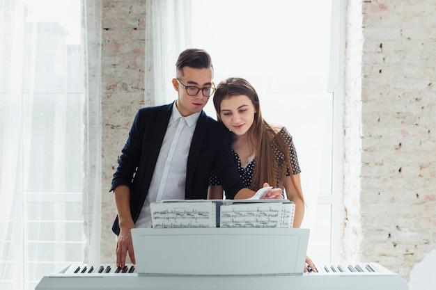 Retrato, de, um, par jovem, olhar, folha musical, aprender, jogar, piano