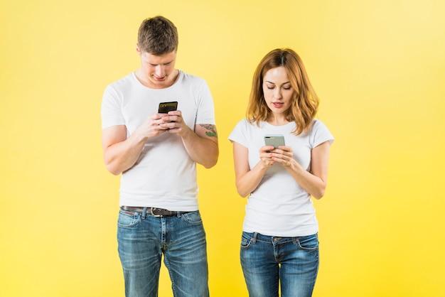 Retrato, de, um, par jovem, texting, ligado, esperto, telefone, contra, amarela, fundo