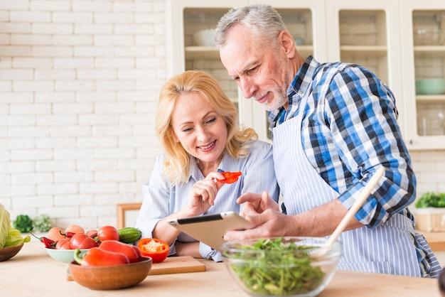 Retrato, de, um, par velho, olhar, tablete digital, enquanto, preparar, a, salada, cozinha