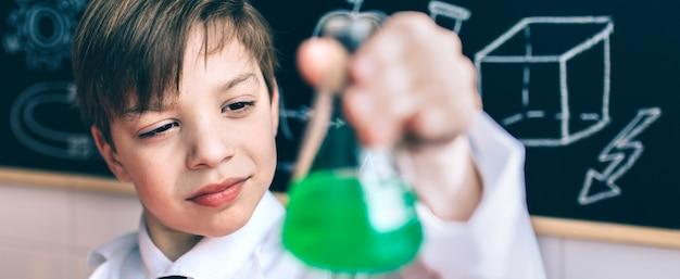 Retrato de um pequeno cientista concentrado procurando um frasco com um líquido químico verde contra um quadro negro desenhado