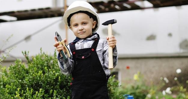 Retrato de um pequeno construtor em um capacete branco com um martelo e um alicate nas mãos