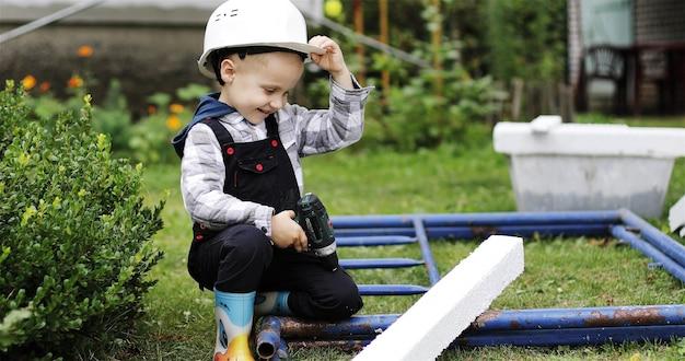Retrato de um pequeno construtor em um capacete branco com uma chave de fenda nas mãos