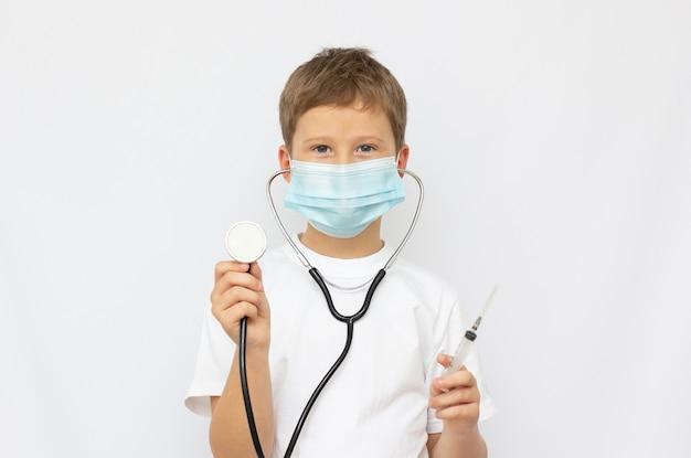 Retrato de um pequeno médico sorridente com estetoscópio e seringa. isolado em fundo branco