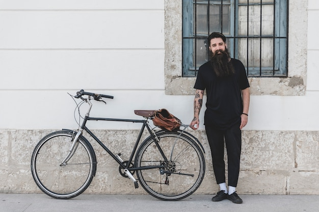 Retrato, de, um, posição homem, com, bicicleta, inclinar-se, parede