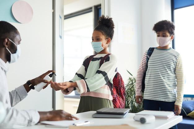 Retrato de um professor ajudando crianças a higienizar as mãos ao entrar na sala de aula na escola, medidas de segurança ambiciosas