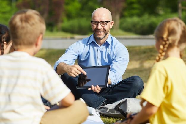 Retrato de um professor careca apontando para a tela do tablet e sorrindo enquanto fala com um grupo de crianças durante a aula ao ar livre sob a luz do sol, copie o espaço