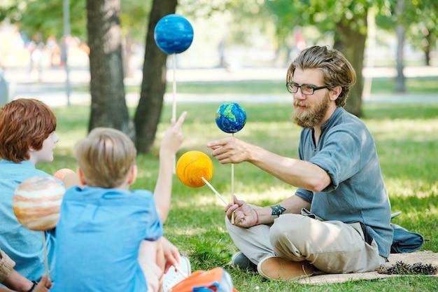 Retrato de um professor careca apontando para a tela do tablet e sorrindo enquanto fala com um grupo de crianças durante uma aula ao ar livre sob a luz do sol