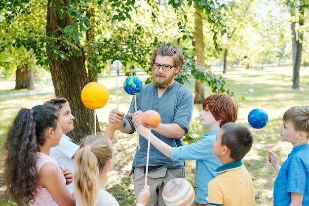 Retrato de um professor careca apontando para o modelo do planeta e sorrindo enquanto conversava com um grupo de crianças durante uma aula ao ar livre sob a luz do sol
