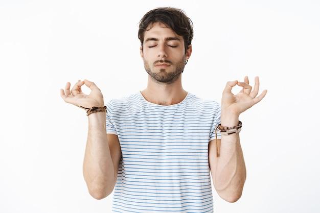 Retrato de um professor de ioga homem bonito calmo e relaxado, em posição de lótus com gesto zen e olhos fechados, meditação para aliviar o estresse, paciente sobre uma parede cinza