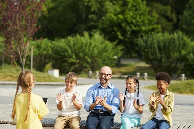 Retrato de um professor sorridente com um grupo de crianças aplaudindo a menina fazendo uma apresentação enquanto desfruta de uma aula ao ar livre sob a luz do sol, copie o espaço