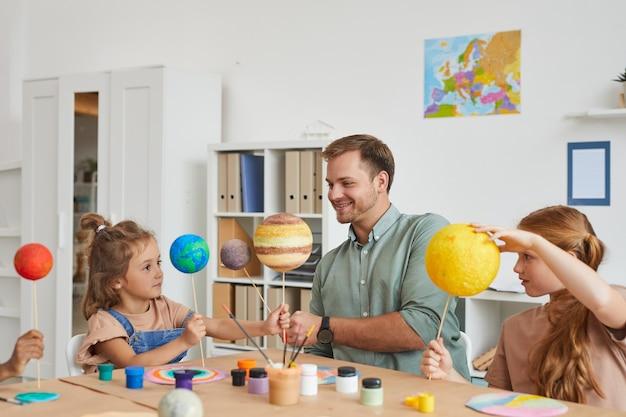 Retrato de um professor sorridente segurando modelos de planetas enquanto trabalhava com um grupo de crianças na aula de arte e artesanato