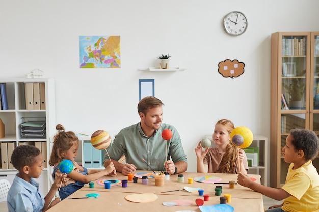 Retrato de um professor sorridente trabalhando com um grupo multiétnico de crianças pintando modelos de planetas em aulas de arte e artesanato