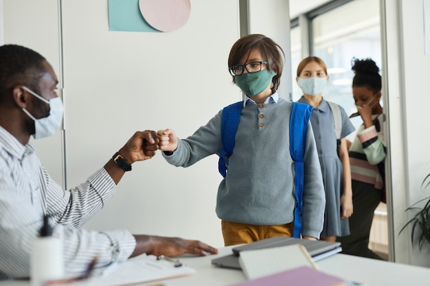 Retrato de um professor usando máscara e batendo os punhos em crianças entrando na sala de aula, medidas de segurança ambiciosas