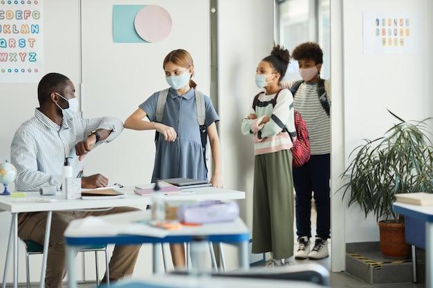 Retrato de um professor usando máscara e cumprimentando crianças entrando na sala de aula, medidas de segurança ambiciosas