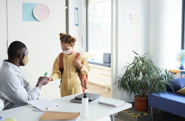 Retrato de um professor verificando a temperatura da garota entrando na sala de aula na escola, medidas de segurança ambiciosas
