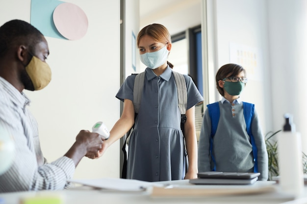 Retrato de um professor verificando a temperatura das crianças que entram na sala de aula na escola, medidas de segurança ambiciosas