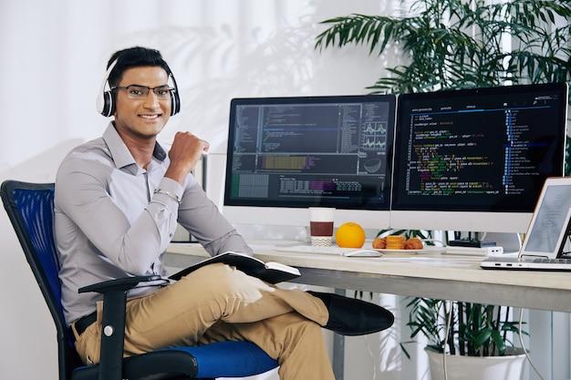 Retrato de um programador indiano confiante e sorridente, sentado em sua mesa de escritório, com código de programação nas telas do computador