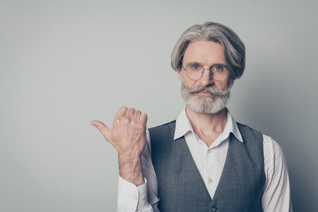 Retrato de um promotor de velhinho descolado e confiante apontando para uma promoção com o dedo