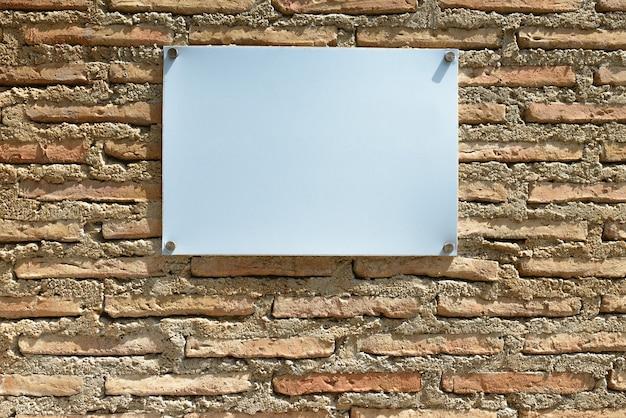 Retrato de um quadro branco em branco com espaço de cópia contra uma parede de tijolos ao ar livre