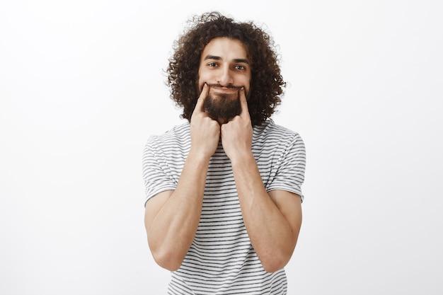 Retrato de um rapaz barbudo hispânico bonito deprimido e infeliz com cabelo encaracolado, sorrindo com os dedos indicadores, tentando parecer positivo enquanto se sente chateado e triste