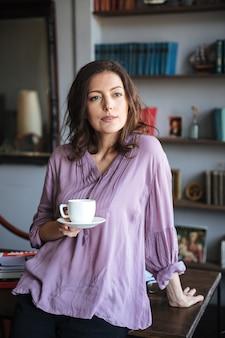 Retrato, de, um, relaxado, mulher madura, segurando xícara café