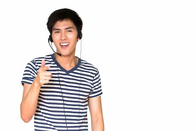 Retrato de um representante de atendimento ao cliente asiático feliz, sorrindo e usando um fone de ouvido isolado contra uma parede branca