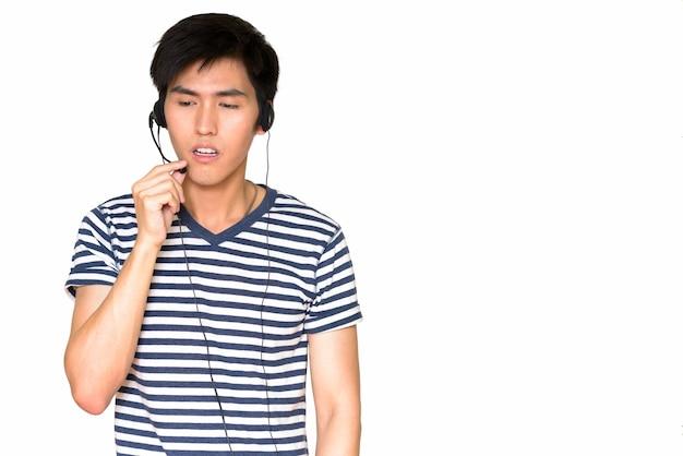 Retrato de um representante de atendimento ao cliente asiático usando um fone de ouvido isolado contra uma parede branca