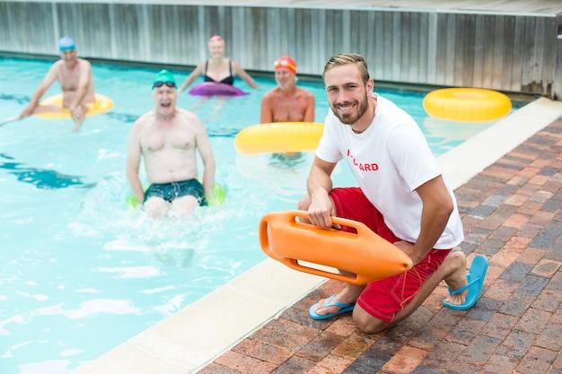 Retrato de um salva-vidas agachado enquanto nadadores nadando na piscina