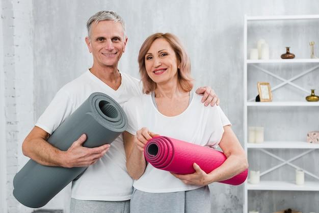 Retrato, de, um, saudável, par velho, com, esteira yoga, ficar, casa