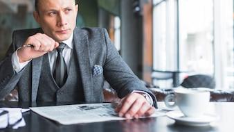 Retrato, de, um, sério, homem negócios, com, jornal, olhando