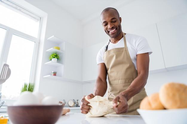 Retrato de um simpático confeiteiro fazendo torta de pão fresco e massa de farinha aprendendo