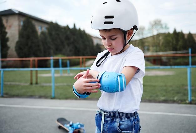 Retrato de um skatista bonito com capacete de segurança e apoios de braço de proteção antes de patinar