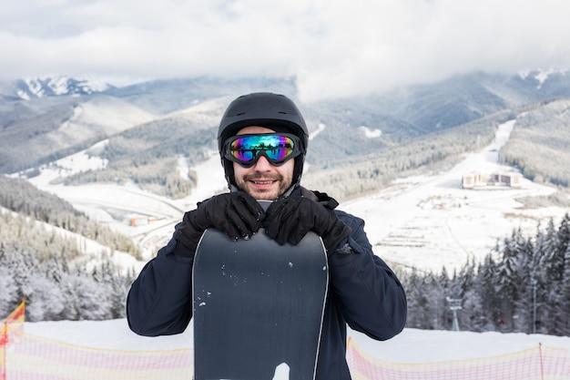 Retrato de um snowboarder alegre no topo de uma pista de esqui na estação de esqui
