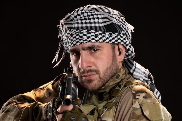 Retrato de um soldado camuflado com metralhadora na parede preta