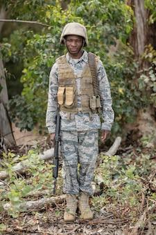 Retrato de um soldado militar confiante em pé com um rifle no campo de treinamento