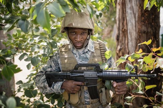 Retrato de um soldado militar confiante guardando com um rifle no campo de treinamento