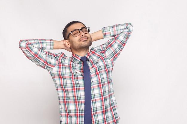 Retrato de um sonhador empresário barbudo bonito na camisa quadriculada, gravata azul e óculos em pé com a mão atrás da cabeça e sorrindo com os olhos fechados. foto de estúdio interno, isolada em fundo cinza