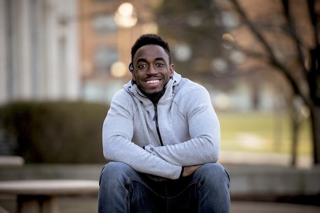 Retrato de um sorridente afro-americano sentado em um parque sob a luz do sol