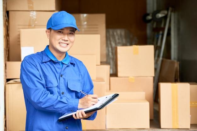 Retrato de um sorridente gerente vietnamita de uma empresa de mudanças de casa, preenchendo documentos depois de entregar uma caixa de papelão com os pertences do cliente