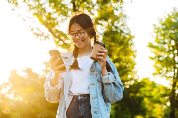 Retrato de um sorridente jovem adolescente alegre estudante caminhando ao ar livre no belo parque verde, bebendo café usando telefone celular.