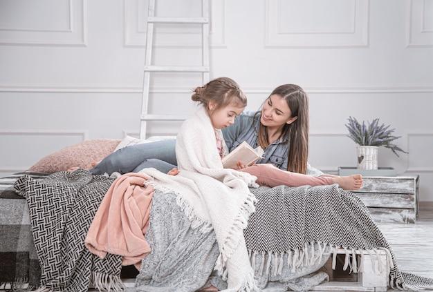 Retrato de um sorridente jovem bonito mãe e filha lendo um livro deitado e relaxe na cama em um quarto branco grande e brilhante.