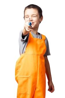 Retrato de um sorridente menino carpinteiro de macacão laranja, posando, segurando uma chave de fenda em um fundo branco e isolado.