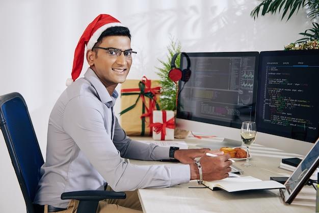Retrato de um sorridente programador indiano com chapéu de papai noel trabalhando no escritório