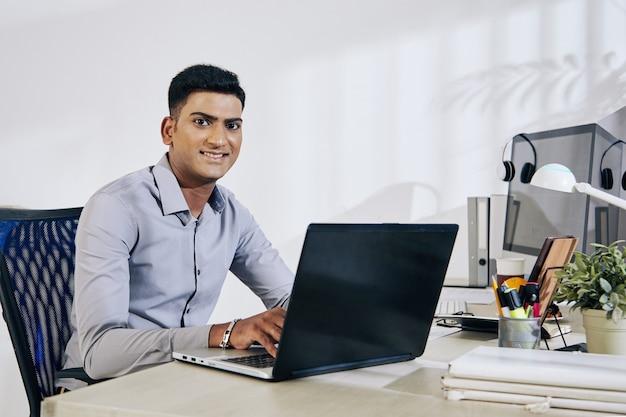 Retrato de um sorridente programador indiano trabalhando em um laptop na mesa do escritório