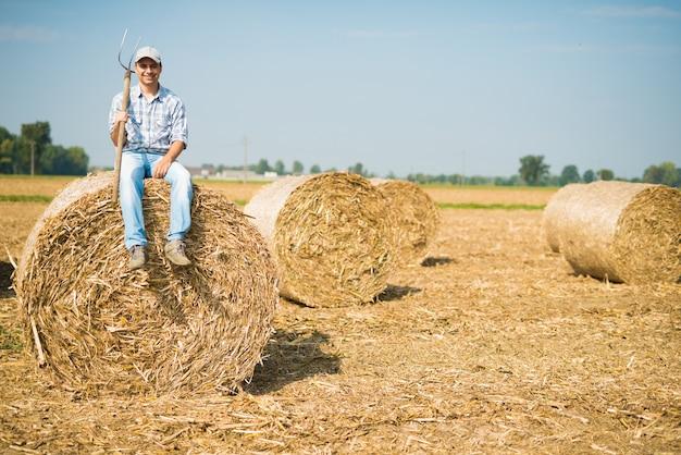Retrato, de, um, sorrindo, agricultor, sentando, ligado, um, feno, pacote, em, seu, campo