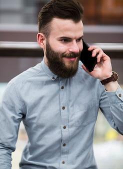 Retrato, de, um, sorrindo, barbudo, homem jovem, falando telefone móvel