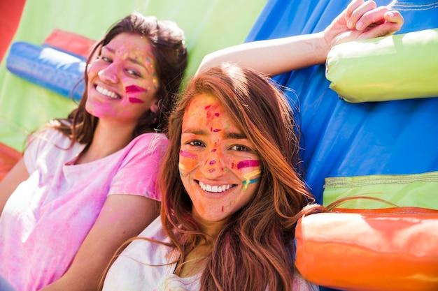 Retrato, de, um, sorrindo, dois, mulheres jovens, com, holi, cor, rosto