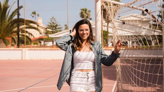 Retrato, de, um, sorrindo, elegante, mulher jovem, ficar, perto, a, rede futebol