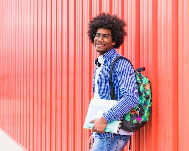 Retrato, de, um, sorrindo, estudante masculino, saco levando, ligado, ombro, e, livros, em, mão, olhando câmera
